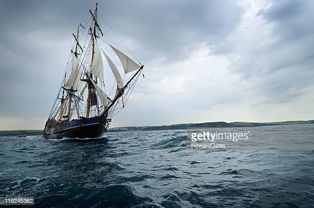 tall ship sailing off the cornwall coast - pirate ship stock photos and pictures