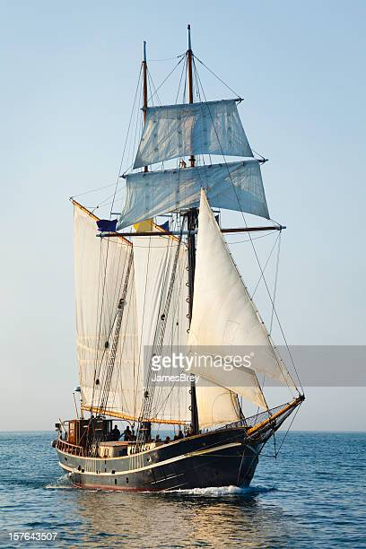tall ship sailing open seas at morning - pirate ship stock photos and pictures
