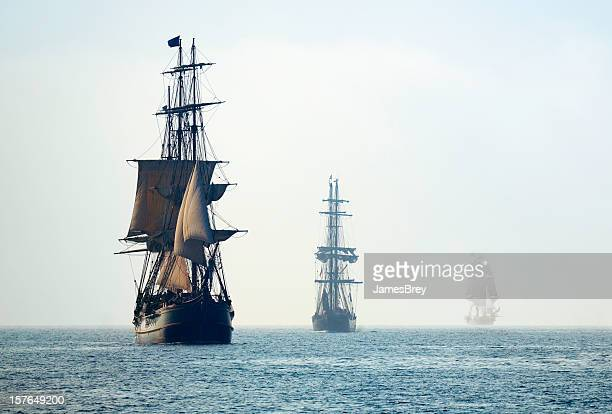 tall ships in the last mists of morning fog - pirate ship stock photos and pictures