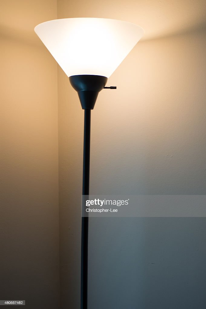 Tall standing lamp turned on : Stock Photo