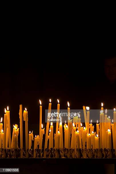Tall thin candles burning in the dark