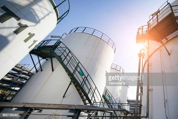 Tall white oil storage tanks