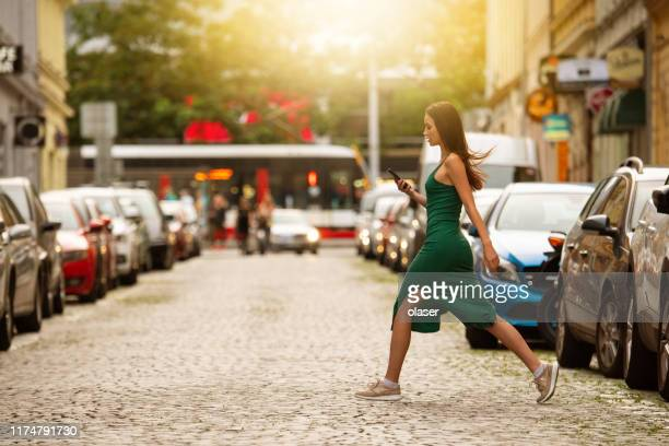 tall woman crossing street, checking phone - tall person stock pictures, royalty-free photos & images