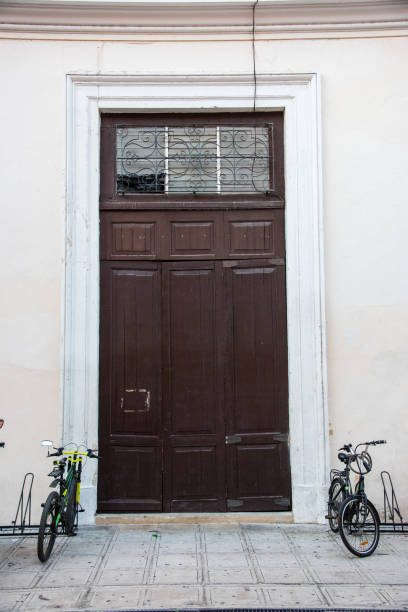 Tall wooden door with bicycles in rack