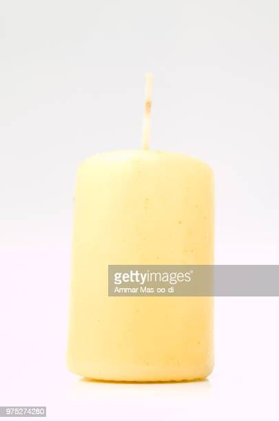 Tall yellow wax candle on white