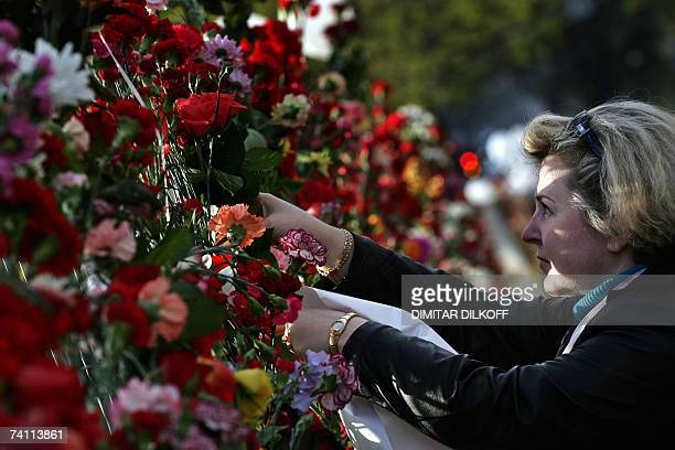 A Russianspeaking woman lays flowers on a fence at the former site of a Soviet Red Army soldier monument in Tallinn 09 May 2007 The Estonian...