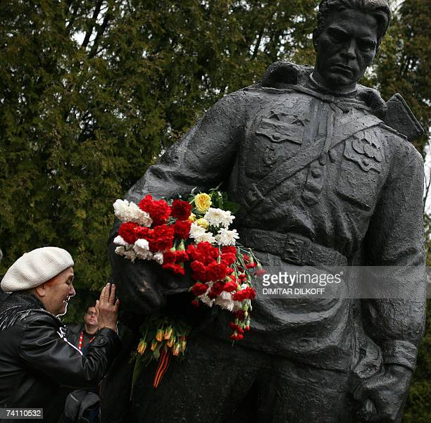 A woman touches the Bronze Soldier monument at the military cemetery in Tallinn 09 May 2007 The Estonian authorities removed a Soviet war monument...