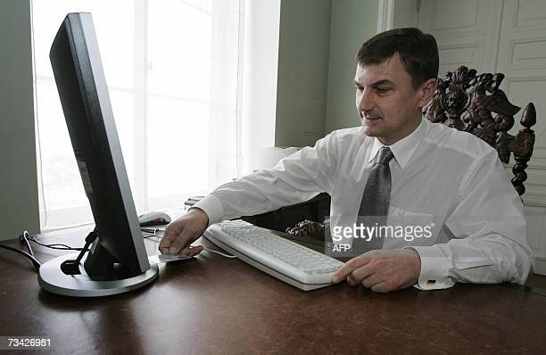 Estonian Prime Minister Andrus Ansip puts a card to validate his electronic ballot through the web 26 February 2007 from his office in advance of...