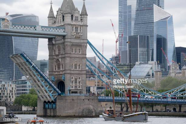 Tall-masted Thames barge passes beneath Tower Bridge that has raised its bascules, on the river Thames, on 11th June 2021, in London, England.