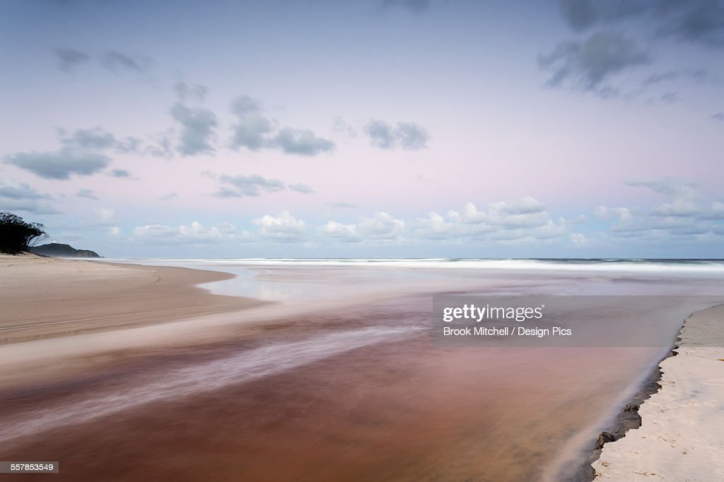 Tallows creek running out into the ocean at a spot known as dolphins at tallows beach after heavy storms : Stock Photo