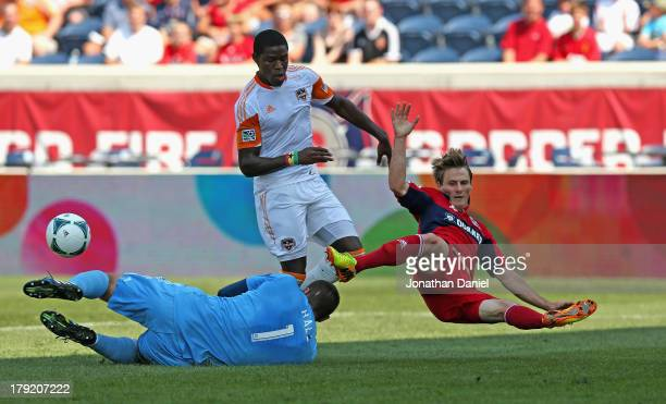 Tally Hall of the Houston Dynamo makes a save against Chris Rolfe of the Chicago Fire as Kofi Sarkodie defends during an MLS match at Toyota Park on...