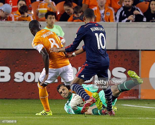 Tally Hall of the Houston Dynamo makes a save in front of Kofi Sarkodie and Teal Bunbury at BBVA Compass Stadium on March 8 2014 in Houston Texas