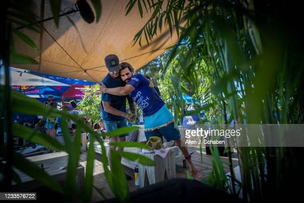 Ítalo Ferreira, 2019 WSL world champion from Brazil, hugs his coach, Mike Parsons, left, while competing in the mens qualifying rounds Saturday at...