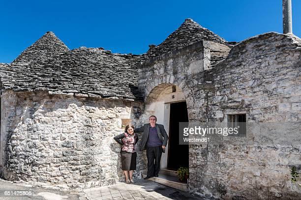 taly, apulia, alberobello, couple in front of trullo - apulien stock-fotos und bilder