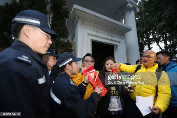 """Tam Tak-chi, Erica Yuen Mi-ming and Albert Chan Wai-yip of People Power attempt to put up """"fai chun"""" outside Government House in Admiralty to demand..."""
