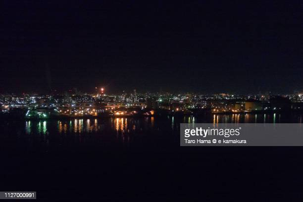 Tama River and factory area of Kawasaki city in Japan night time aerial view from airplane
