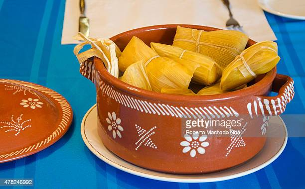 Tamal or tamales Traditional Cuban cuisine in clay pots on a table with a blue tablecloth Tamales are a very popular Latin American meal