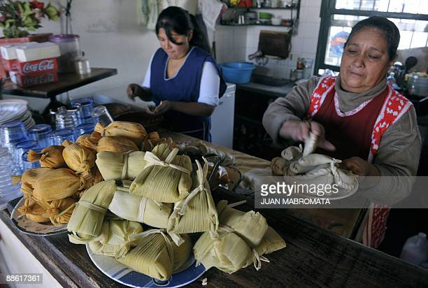 Tamales and humitas are displayed in a bar as women prepare empanadas at a typical eating place in Salta at the foothills of the Andes mountain range...