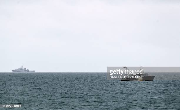 Tamar , a Batch 2 river-class offshore patrol vessel of the British Navy, is watched by a fishing boat as it patrols the waters off the British...
