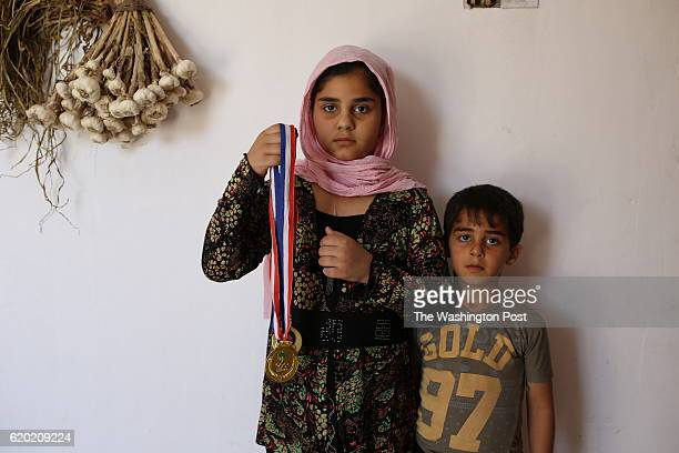 Tamara Adel 10 years old stands with her brother Ahmed Adel 5 years old holds medals of her football player Waleed Adel 16 years old who got killed...