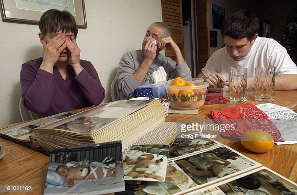 Tamara <cq> and Glen <cq> Osborn <cq> look through a collection of photos with their 19-year-old son Jeff <cq> at their home in Seattle, WA. The...