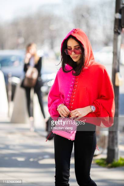Tamara Kalinic is seen wearing two tone red pink hoody Balenciaga mini bag black cropped pants outside Unravel Project during Paris Fashion Week...