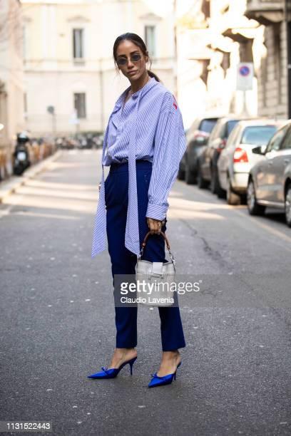 Tamara Kalinic wearing striped Balenciaga shirt blue pants and white bag is seen outside Blumarine on Day 3 Milan Fashion Week Autumn/Winter 2019/20...