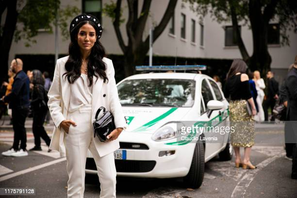Tamara Kalinic, wearing white suit, poses outside the Emporio Armani show during Milan Fashion Week Spring/Summer 2020 on September 19, 2019 in...