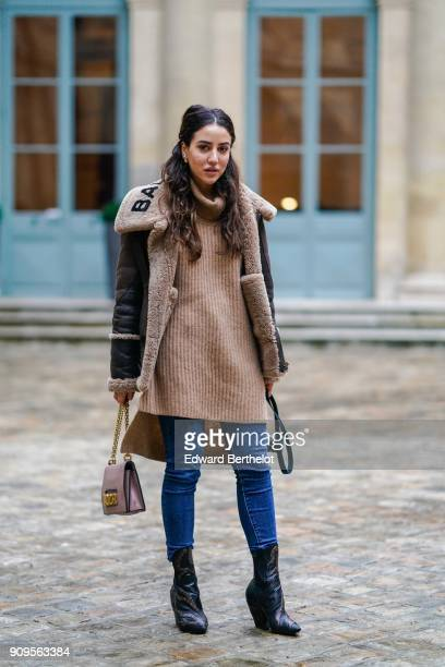 Tamara Kalinic wears a Balenciaga aviator jacket a wool pull over turtleneck blue jeans a bag black boots during Paris Fashion Week Haute Couture...
