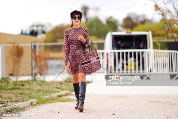 Tamara Kalinic wears a black beret hat sunglasses a Dior tote bag a pink and black dress thigh high leather boots outside Dior during Paris Fashion...