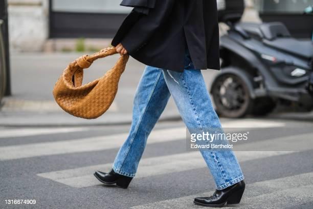 Tamara Kalinic wears a black oversized ripped Margiela blazer jacket, blue faded denim oversized Margiela jeans pants, a brown shiny leather braided...