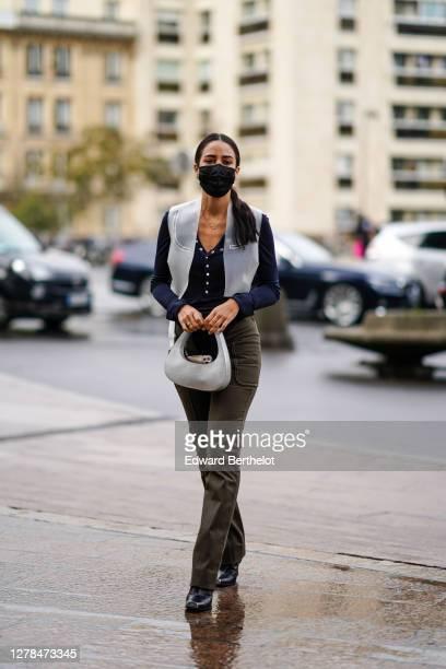 Tamara Kalinic wears a black protective face mask, a gray leather bag, khaki pants, a gray sleeveless jacket, a dark blue top, leather shoes, outside...