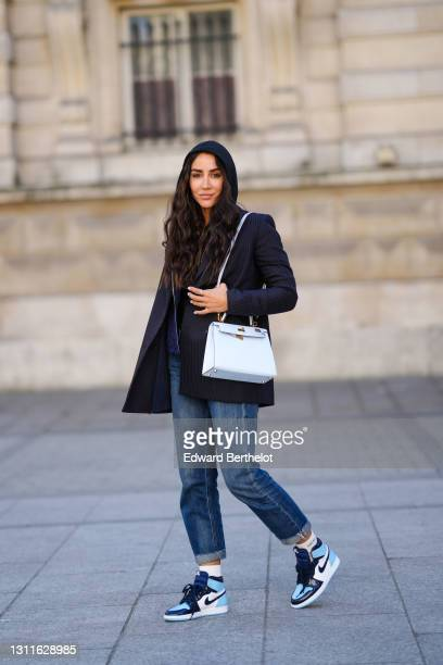 Tamara Kalinic wears a black striped oversized blazer jacket from Stella McCartney, a navy blue hoodie sweater from Vuitton, a black top, a pastel...