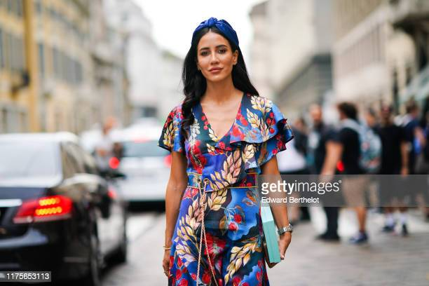 Tamara Kalinic wears a blue headband, a floral print colored dress, a turquoise clutch, outside the Peter Pilotto show during Milan Fashion Week...