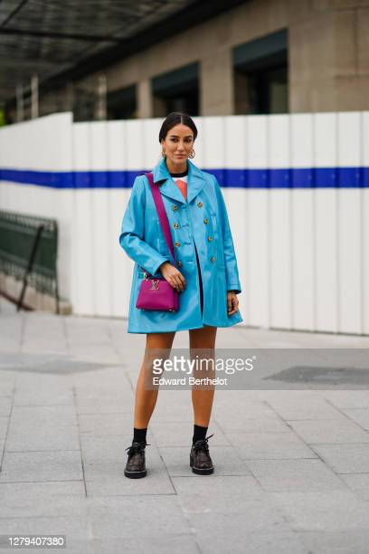Tamara Kalinic wears a blue shiny pvc coat, a pullover, a short skirt, a purple Vuitton leather bag, black socks, brown leather Vuitton monogram...