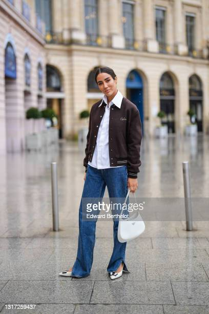Tamara Kalinic wears a brown Celine teddy jacket, a white shirt, blue long flared slit denim jeans pants, a white Prada Cleo bag, black and white...