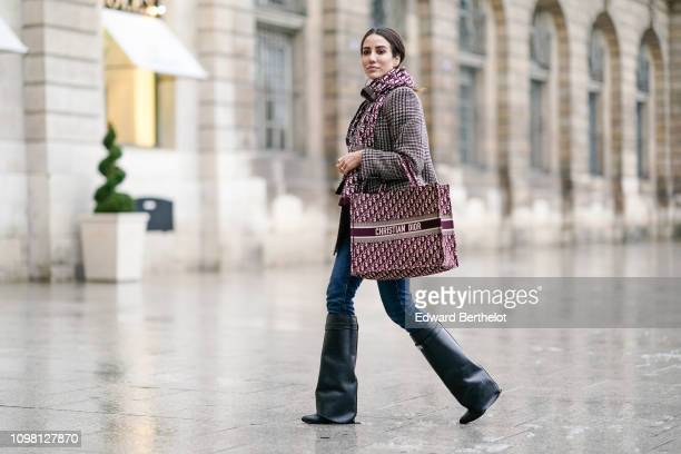 Tamara Kalinic wears a checked blazer jacket, a Dior scarf, blue jeans, black leather high boots, holds a Dior tote bag, outside Alexis Mabille,...