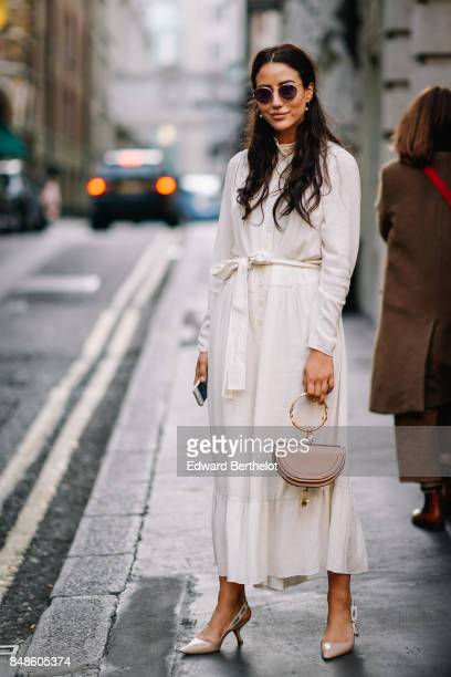 Tamara Kalinic wears a Chloe bag sunglasses a white ruffled dress heels shoes outside Peter Pilotto during London Fashion Week September 2017 on...