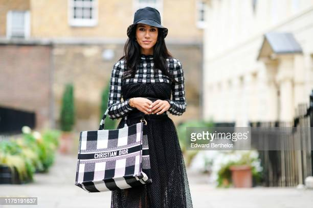 Tamara Kalinic wears a dark hat, a black and white checked dress with a black lace mesh pleated part, a leather large belt, a black and white checked...