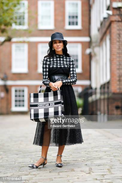Tamara Kalinic wears a dark hat a black and white checked dress with a black lace mesh pleated part a leather large belt a black and white checked...