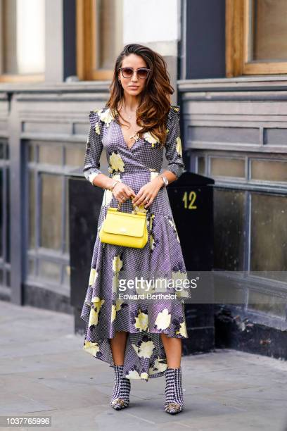 Tamara Kalinic wears a dress with yellow floral print and ruffles a yellow bag black and white shoes during London Fashion Week September 2018 on...