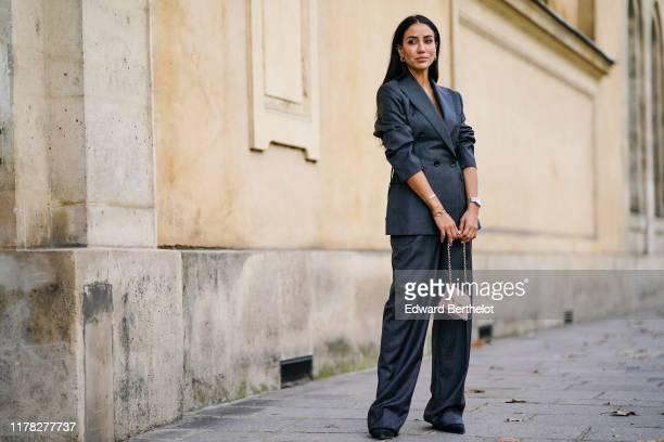Tamara Kalinic wears a gray blazer jacket, a golden ring necklace, a pink bag, flare pants, earrings, outside Beautiful People, during Paris Fashion...