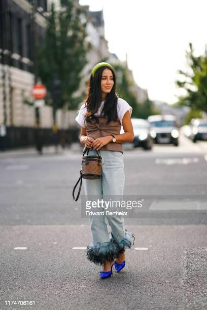 Tamara Kalinic wears a neon green headband a white tshirt a brown fabric corset a watch golden bracelets a Vuitton brown monogram logo bag pale blue...