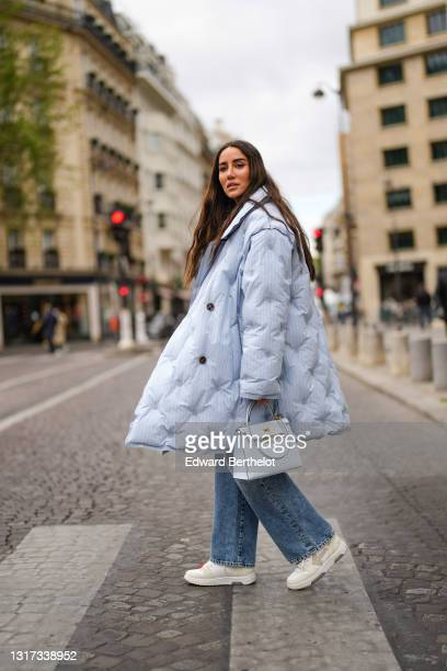 Tamara Kalinic wears a pale blue long quilted winter coat from Margiela, blue denim wide-leg jeans pants from Margiela, sneakers shoes with zip-tie...