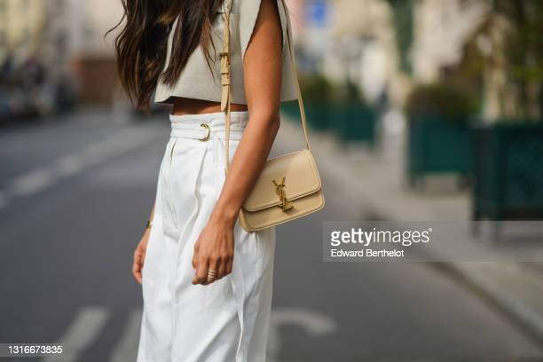 Tamara Kalinic wears a pale gray Jacquemus V-neck collar crop top with epaulets, white large flared Philosophy belted trousers pants, a gold Love...