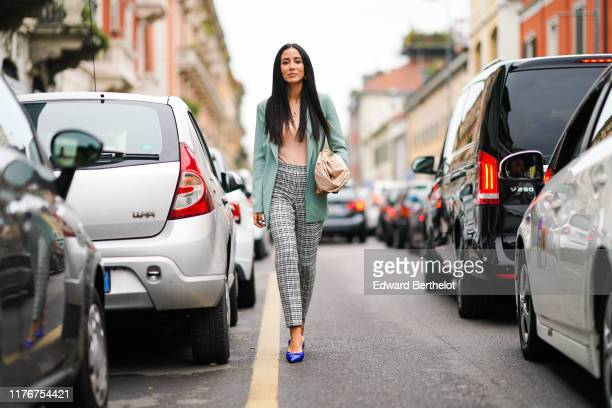 Tamara Kalinic wears a pale green blazer jacket, a pink top, a golden necklace, checked pattern pants, blue pointy shoes, a bag, outside the Boss...