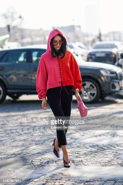 Tamara Kalinic wears a pink and red bi color hoodie sweater sunglasses black pants a pink Balenciaga bag outside Unravel Project during Paris Fashion...