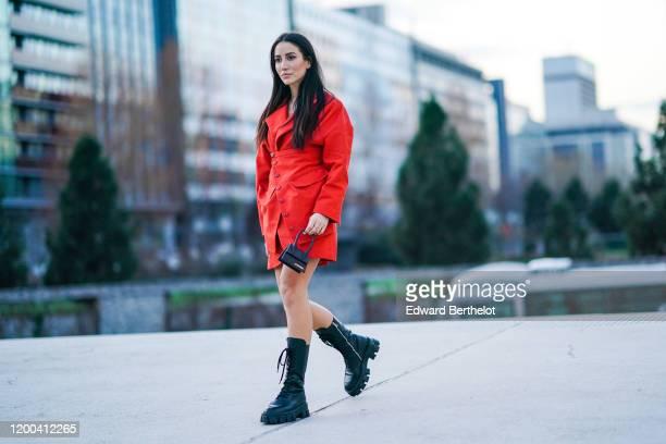 Tamara Kalinic wears a red dress/coat, a Jacquemus mini bag, black boots, outside Jacquemus, during Paris Fashion Week - Menswear F/W Fall/Winter...