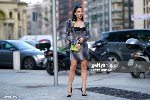 Tamara Kalinic wears a shiny bejeweled dress with shoulder pads, a green snake pattern printed bag, pointy shoes, outside Versace, during Milan...