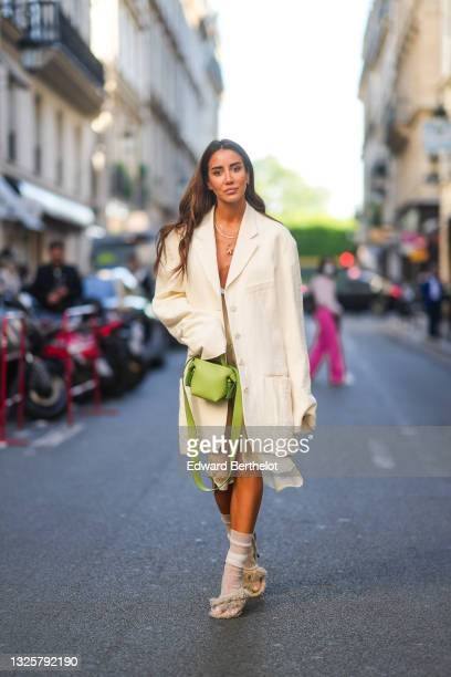 Tamara Kalinic wears a total Acne Studios look, made of a necklace, a white long oversized blazer jacket, a white transparent silky midi dress, a...